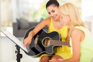 music teacher tutoring young girl to play guitar