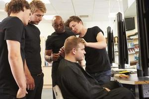 profesor ayudando a estudiantes a entrenarse para convertirse en peluqueros