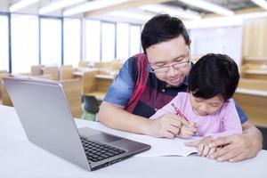 maestro de escuela primaria ayuda a su alumno foto