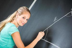 Pretty young teacher writing on the blackboard