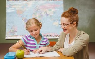 maestro ayudando a la niña con la tarea en el aula