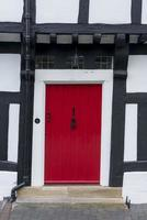Red front door in a timber framed Tudor house photo