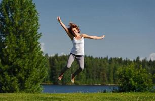 Young woman jumping outside photo