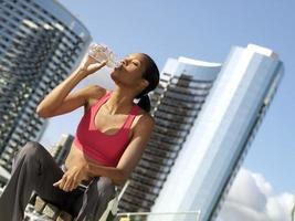 woman taking break from exercising outdoors, drinking water