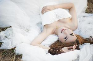 Portrait of a lovely maiden lying on the grass field photo