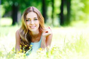 jonge vrouw in blauwe jurk liggend op gras