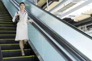 Business woman using the escalator