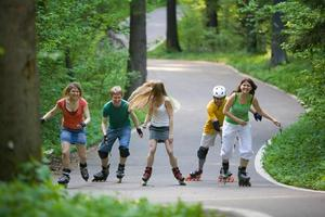 Group of teenagers rollerblading on path in a park
