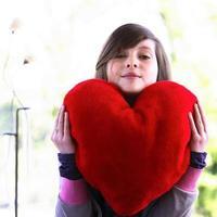 menina adolescente, segurando um coração vermelho