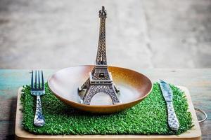 Eiffel model on table setting of plate, fork, knife.