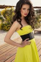 mooie brunette in gele jurk ontspannen op het strand