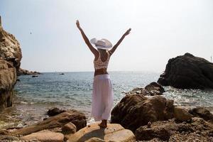Dama con sombrero y vestido de encaje blanco en la playa rocosa