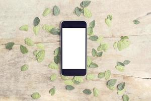 Blank smartphone screen with leaves on wooden table, mock up photo