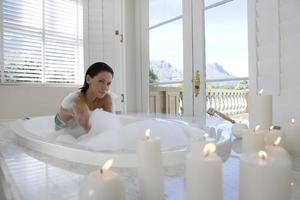 mujer joven en baño de burbujas, retrato, velas encendidas para foto
