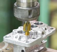 operator machining automotive parts by machining center photo