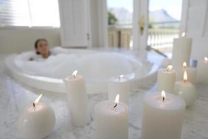 mujer joven en baño de burbujas, velas iluminadas en primer plano foto