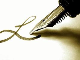 pluma estilográfica escribiendo en tinta sobre papel blanco foto