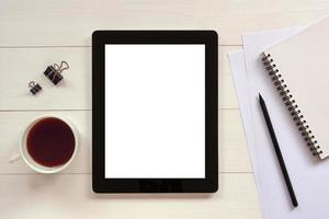 Tablet with white blank empty screen on wooden table photo