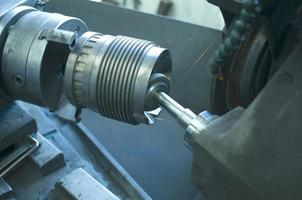 Machining lathe turning steel in a manufacturing plant photo