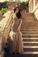 mujer con cabello negro en lujoso vestido posando en las escaleras