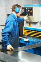 worker operating guillotine shears machine photo