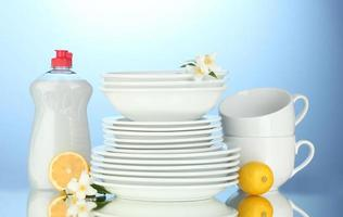 empty clean plates and cups with dishwashing liquid and sponges