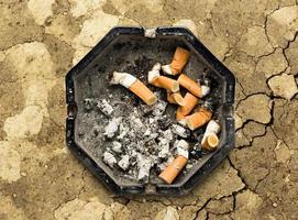 cenicero con colillas de cigarrillos foto