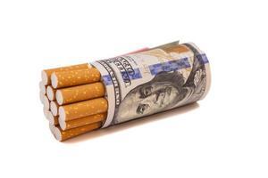 Cigarrillos y dinero sobre un fondo blanco. foto
