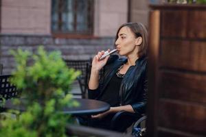 hermosa glamorosa morena fumar cigarrillo electrónico foto