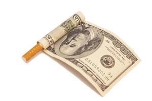 Cigarrillo y billete de cien dólares sobre fondo blanco. foto