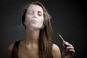 Elegant woman smoking e-cigarette with smoke photo