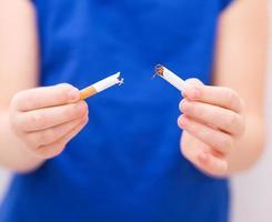 jovencita está rompiendo un cigarrillo