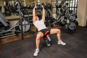 Young man doing Dumbbell Incline Bench Press workout in gym photo