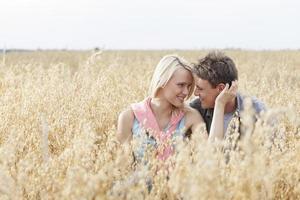 jovem casal olhando um ao outro enquanto relaxa no meio do campo