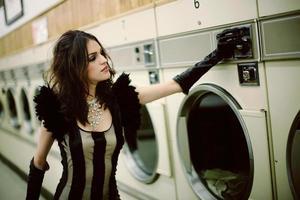 bruna con abito nero e guanti in stuoia per il bucato