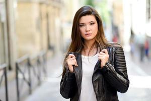 hermosa mujer japonesa en fondo urbano con chaqueta de cuero foto