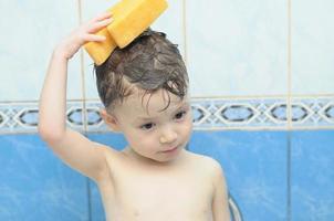 jongen wast zijn hoofd met spons