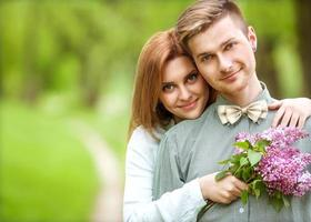 pareja de enamorados en el parque sonriendo sosteniendo un ramo
