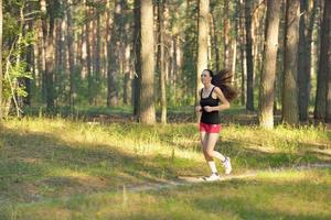 Woman jogging in forest photo