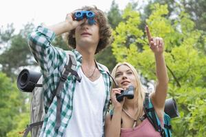 excursionista masculino utilizando binoculares mientras novia mostrando algo en el bosque