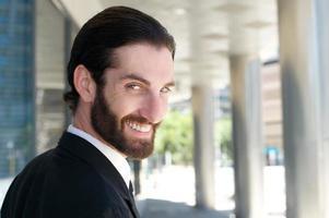 apuesto joven con barba sonriendo afuera foto