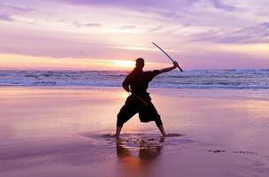 Young samurai women with Japanese swordn on the beach
