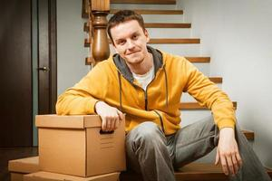 Moving house. Young man with cardboard boxes on a stairs. photo