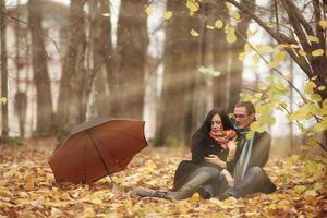 jeune famille dans la forêt d'automne au soleil