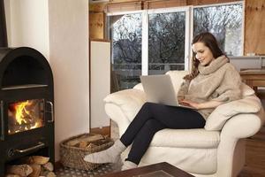 mujer joven en casa en silla usando laptop