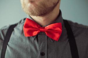 rosto barbudo e uma gravata vermelha na camisa