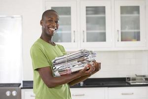 Joven con manojo de periódicos en la cocina, sonriendo, portrai