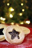 3 dusted mince pies on red table cloth at Christmas