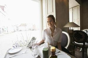 Portrait of smiling female customer sitting at restaurant table