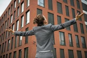 Geschäftsfrau freut sich vor Bürogebäude. Rückansicht